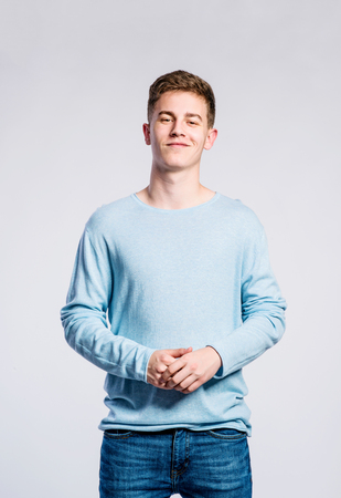 Teenage boy in jeans and blue sweatshirt, young man, studio shot on gray background