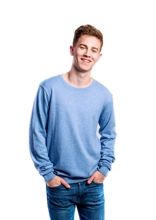 Teenage boy in jeans and blue sweatshirt, young man, studio shot on white background, isolated