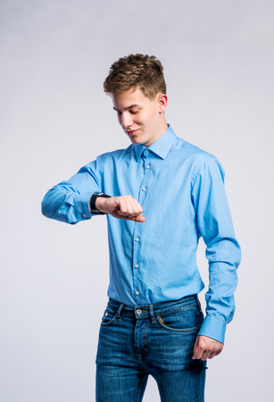 looking at watch: Teenage boy in jeans and blue shirt, young man, studio shot on gray background