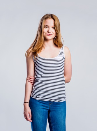 Teenage girl in jeans and blue tank top, young woman, studio shot on gray background