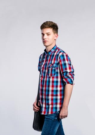 uomo felice: L'adolescente in jeans e camicia a quadri, giovane uomo, girato in studio su sfondo grigio Archivio Fotografico