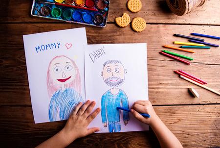 彼女の母親と父親の絵を描く認識できない子の手。木製の背景で撮影スタジオ。