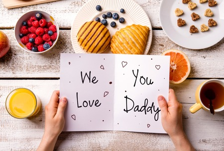 Fathers day composition. Hands of unrecognizable man holding greeting card with We love you, Daddy, text. Breakfast meal. Studio shot on wooden background. Stock Photo