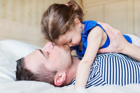 fun day: Young father having fun with his cute little daughter, lying in bed