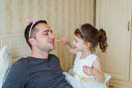 father daughter: Cute little girl in princess dress that is putting on colorful make up on her father Stock Photo