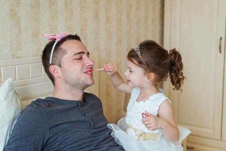 padre e hija: Niña linda en el vestido de la princesa que está poniendo en colorido compone en su padre Foto de archivo