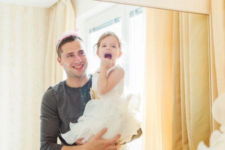dress up: Cute little girl in princess dress that putt on colorful make up on her father, looking into a mirror
