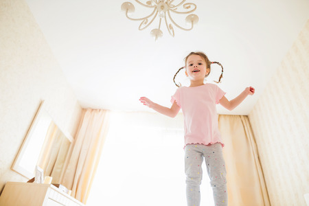 chandelier  kids: Cute little girl in pink t-shirt with two braids in bedroom jumping on a bed