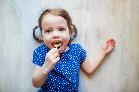 lolli: Cute little girl with two braids lying on the floor, smiling, eating spaghetti