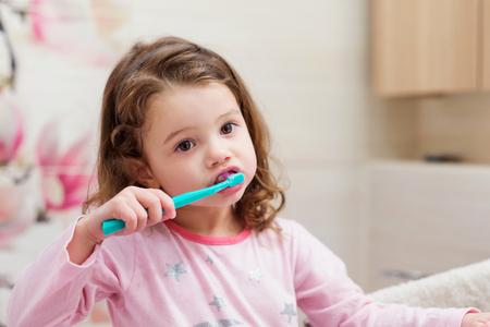 Cute little girl in pink pyjamas in bathroom brushing her teeth