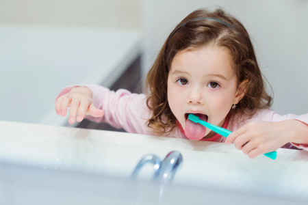 Schattig klein meisje in het roze pyjama's in de badkamer haar tanden poetsen