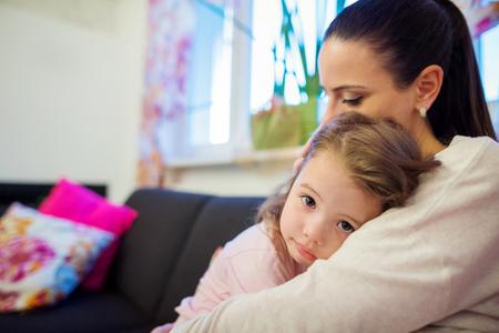niños tristes: Joven madre sosteniendo a su pequeña hija triste en sus brazos Foto de archivo