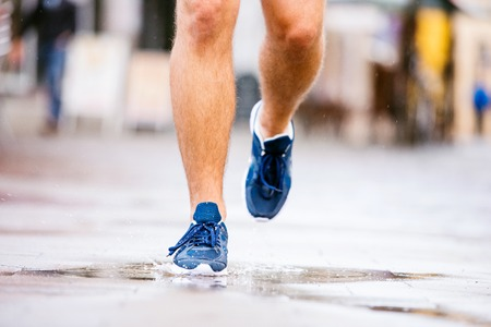outdoor pursuit: Close up of young hipster runner in town with water bottle, drinking