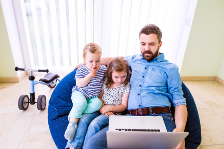 bean bag: Father and daughters together, playing on laptop, sitting on bean bag, high angle view Stock Photo
