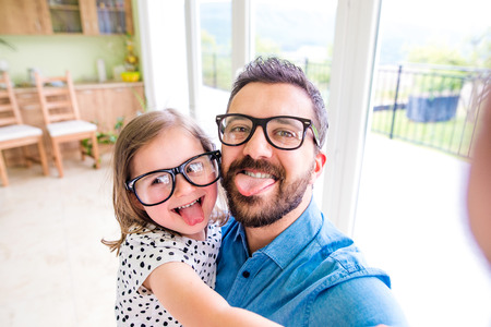 Father with his little daughter in black hipster eyeglasses, making funny face, sticking tongue out, sunny day indoors 版權商用圖片