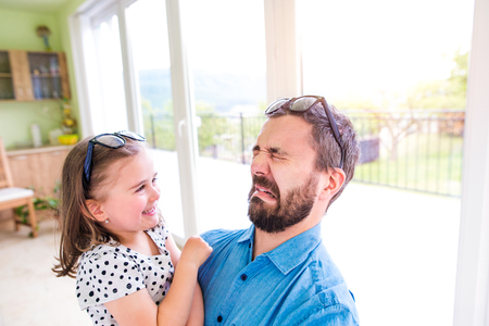 funny face: Father holding his little daughter, making funny face, sunny day indoors Stock Photo