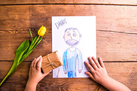 Fathers day composition. Hands of unrecognizable child holding a drawing of her father and little gift. Yellow tulip. Studio shot on wooden background.