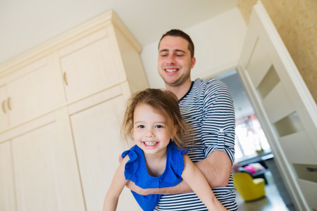 kids having fun: Young father having fun with his cute little daughter, holding her, carrying her Stock Photo