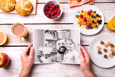 cereals holding hands: Fathers day composition. Hands of unrecognizable man holding black and white picture of him and his daughter taking selfie. Breakfast meal. Studio shot on white wooden background. Stock Photo