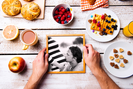 photo frame: Fathers day composition. Hands of unrecognizable man holding black and white picture of him and his pregnant wife in picture frame. Breakfast meal. Studio shot on white wooden background.