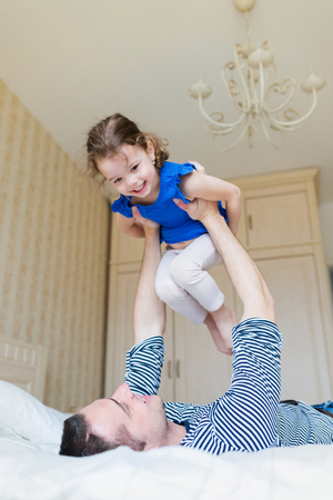 chandelier  kids: Young father having fun with his cute little daughter, lying on bed, lifting her up in the air. Stock Photo