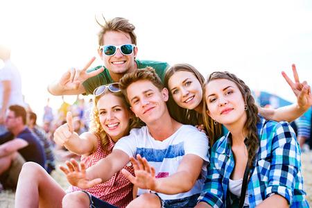 Groep van tiener jongens en meisjes in de zomer muziekfestival, zittend op de grond Stockfoto