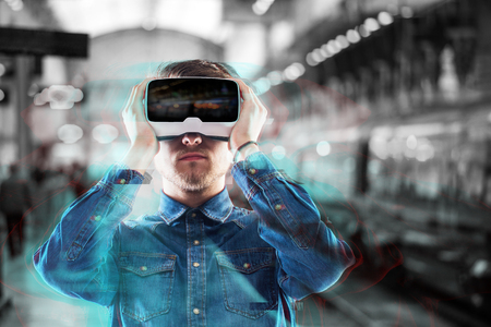 subway station: Hipster man in denim shirt wearing virtual reality goggles standing on subway station. Stock Photo