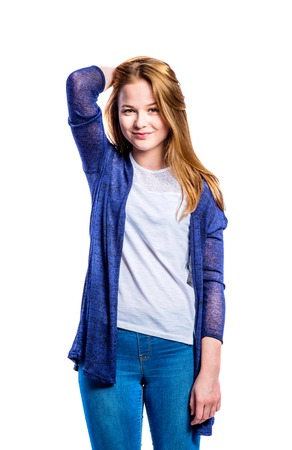 Teenage girl in jeans and long blue sweater, young woman, studio shot on white background, isolated