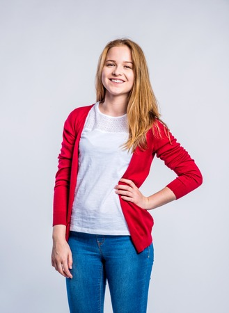 red cardigan: Teenage girl in jeans and red cardigan, young woman, studio shot on gray background