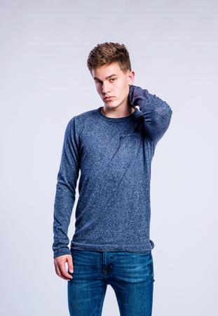 sudadera: adolescente en pantalones vaqueros y una sudadera azul, joven, tiro del estudio sobre fondo gris