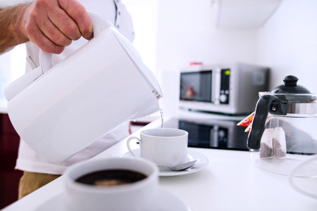electric kettle: Unrecognizable man preparing coffee. Pouring hot water from electric kettle into prepared cups.