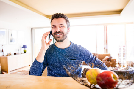 homeoffice: Businessman in blue long sleeved t-shirt working from home, holding smartphone, making phone call