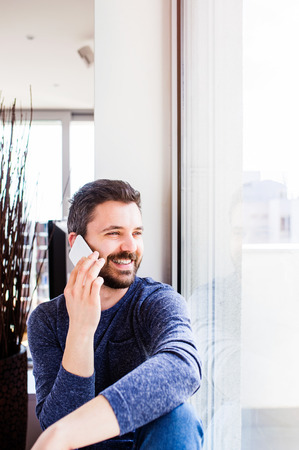 long sleeved: Businessman in blue long sleeved t-shirt working from home, holding smartphone, making phone call