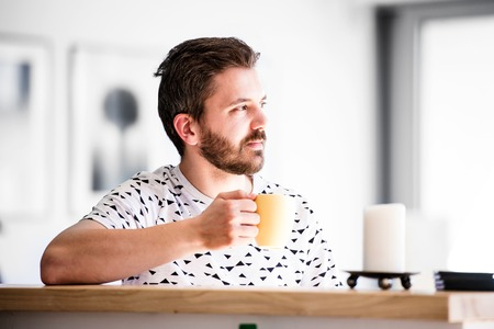 homeoffice: Handsome hipster businessman working from home, taking a break, drinking coffee
