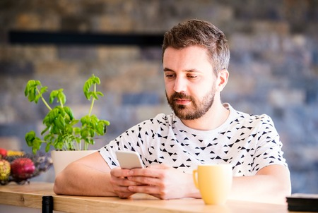 homeoffice: Hipster businessman in white t-shirt working from home, holding smart phone, texting Stock Photo