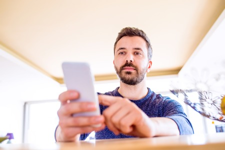 person reading: Hipster businessman in blue long sleeved t-shirt working from home, holding smart phone, texting