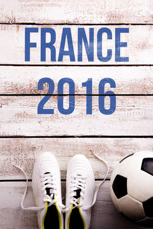 cleats: Soccer ball, cleats and France 2016 against wooden floor, studio shot on white background.