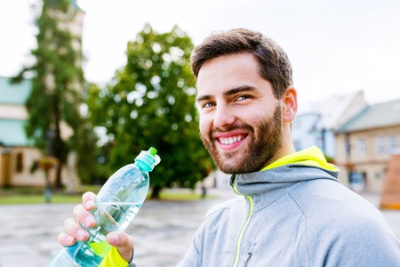 water town: Close up of young hipster runner in town with water bottle, drinking