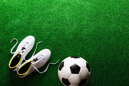 cleats: Soccer ball and cleats against artificial turf, studio shot on green background. Copy space. Stock Photo