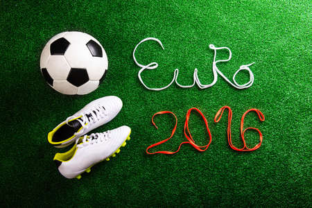 cleats: Soccer ball, cleats and Euro 2016 sign made of shoelaces against artificial turf, studio shot on green background.