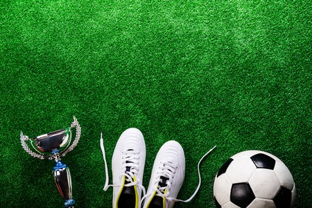 soccer cleats: Soccer ball, cleats and trophy against artificial turf, studio shot on green background. Copy space.