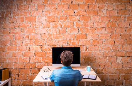 비즈니스 사람 벽돌 벽에 기대어 사무실 책상에 앉아. 테이블에 컴퓨터입니다. 커피 컵, 개인 주최자 및 직장 주위 다양 한 사무실 물건. 배면도.