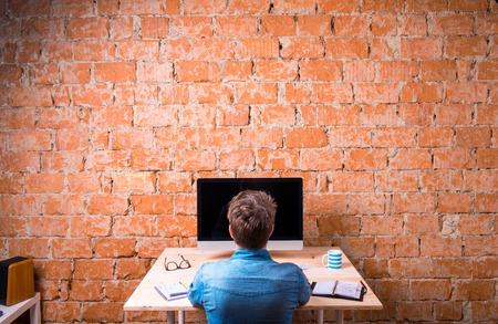 Bedrijfs persoon zit op kantoor bureau, werken, tegen bakstenen muur. Computer op de tafel. Kopje koffie, personal organizer en diverse office stuff rond de werkplek. Achteraanzicht.