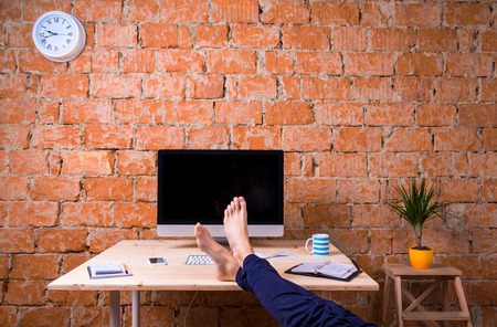 feet on desk: Feet of unrecognizable businessman sitting at his office desk. Brick wall background. Smart phone, tablet and various office supplies around the workplace. Flat lay. Stock Photo