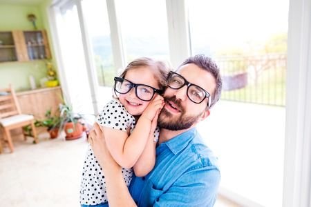 dad and daughter: Father with his little daughter in black hipster eyeglasses, sunny day indoors