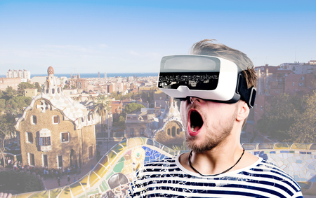 VIRTUAL REALITY: Hipster man in striped black and white sweatshirt wearing virtual reality goggles. Park Guell, Barcelona, Spain. Stock Photo
