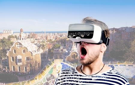 Hipster Mann in gestreiften schwarzen und weißen Sweatshirt trägt Virtual Reality Brille. Park Güell, Barcelona, ??Spanien.