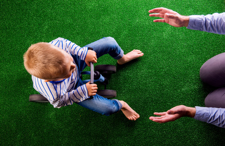 Unrecognizable father catching his little son that is riding a bike, against artificial grass. Studio shot on green background. Stock Photo