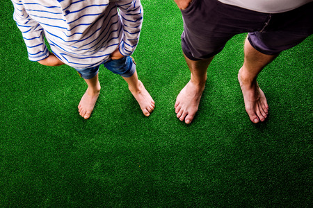 Legs of unrecognizable father and son standing, against artificial grass. Studio shot on green background. Copy space.