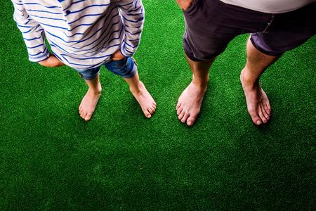 Beine der unerkennbaren Vater- und Sohnstellung, gegen künstliches Gras. Atelieraufnahme auf grünem Hintergrund. Kopieren Sie Platz. Standard-Bild - 57859625